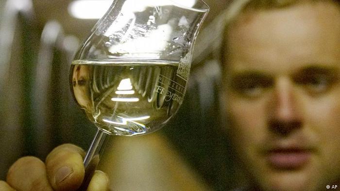 Mann hält ein Glas Weißwein in der Hand und blickt es kritisch an. (AP)