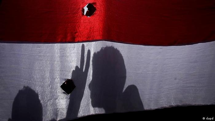 The shadow of an anti-government protestor is cast on his national flag as he flashes the victory sign