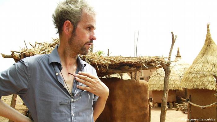 Christoph Schlingensief in seinem Operndorf in Ouagadougou, Burkina Faso, vor Strohhütten