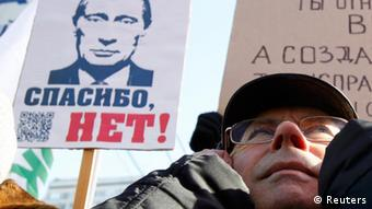A protester takes part in a demonstration for fair elections on Novy Arbat Street in central Moscow March 10, 2012. People gathered to protest against violations during the parliamentary elections in December 2011 and at the recent presidential elections on March 4, according to organizers. The board (L) displays an image of Russia's Prime Minister Vladimir Putin and reads 12 years more? Thanks, no! REUTERS/Sergei Karpukhin (RUSSIA - Tags: POLITICS CIVIL UNREST ELECTIONS)