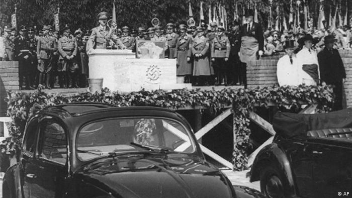 HITLER DURING HIS CORNERSTONE-LAYING-SPEECH - Fallersleben near Hannover, Germany, May 26, 1938. After a speech of Adolf Hitler, the Fuehrer, laid the cornerstone for the giant automobile-works-to-be which are to turn out the cheap peoples car-supposed to be the cheapest car of the world. FOTO SHOWS: Hitler during his speech. Second at right of him is Dr. Porsche, the constructor of the Volkswagen, first models of which can be seen in the foreground. (AP-Photo)