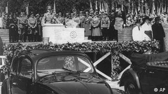Hitler gives a speech before cars as Nazis look on