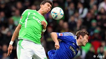 Mario Mandzukic, then of Wolfsburg, battles Bayer Leverkusen's Stefan Reinartz (right) for the ball a Bundesliga match between the two sides last season