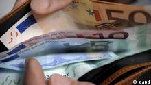 Berlin/ ARCHIV: Eine Frau zaehlt in Berlin fuer eine Fotoillustration Euro-Banknoten in einer Geldboerse (Foto vom 17.06.08). Die Euro-Finanzminister haben sich in der Nacht zum Dienstag (21.02.12) im Grundsatz auf das zweite Rettungspaket fuer Griechenland geeinigt. Demnach soll der Beitrag der Europartner von 130 Milliarden Euro nicht erhoeht werden. Das urspruengliche Ziel, Athens Gesamtschuldenlast bis 2020 von mehr als 160 auf 120 Prozent der Wirtschaftskraft zu reduzieren, wurde der Quelle zufolge nur minimal auf 120,5 Prozent nach oben korrigiert. Der Euro legte nach den ersten Meldungen schlagartig um 0,7 Prozent auf 1,328 Dollar zu. (zu dapd-Text) Foto: Michael Gottschalk/dapd