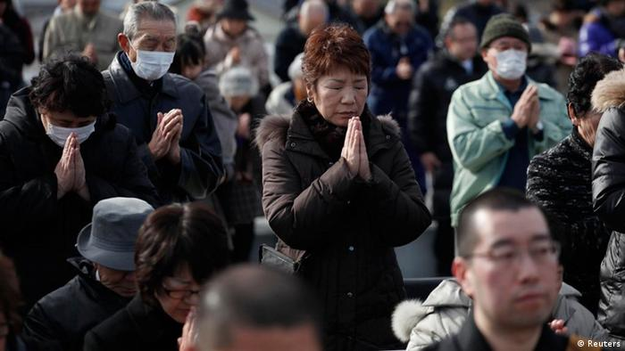 People take part in a moment of silence at 2:46p.m. (0546 GMT) during a ceremony at an area damaged by the March 11, 2011 earthquake and tsunami in Ofunato, Iwate Prefecture, March 11, 2012, to mark the first anniversary of the disaster that killed thousands and set off a nuclear crisis. REUTERS/Carlos Barria (JAPAN - Tags: DISASTER ANNIVERSARY)
