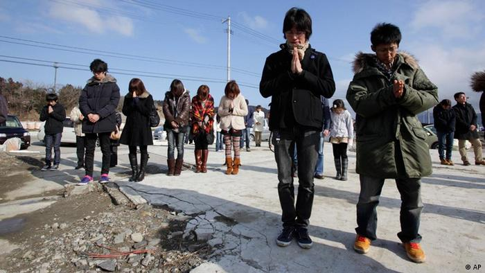 Japanese people bowing their heads in prayer while observing a minute's silence in front of the remains of the disaster control center