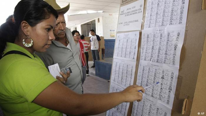 An electoral worker, left, helps a voter during legislative and municipal elections in Verapaz, El Salvador