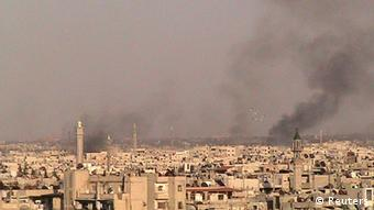 Smoke rises from the Jab Al-Jandli district of Homs