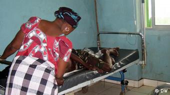 Mulher cuida de parente no Hosptial Simão Mendes, em Bissau: fim de financiamento do Fundo Mundial pode levar muitos pacientes a abandonar tratamento no país