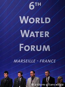 Representatives stand in front of a World Water Forum banner