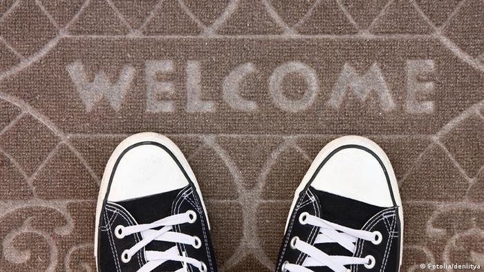 Fußmatte mit der Aufschrift Willkommen, davor schwarz-weiße Turnschuhe (Foto: Fotolia/denlitya)