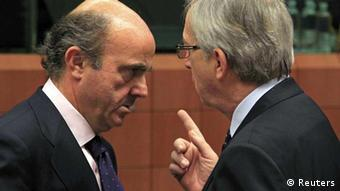 Spain's Economy Minister Luis de Guindos (L) talks with Luxembourg's Prime Minister and Eurogroup chairman Jean-Claude Juncker at a Eurogroup meeting in Brussels March 12, 2012. Euro zone finance ministers will sign off on a second bailout for Greece on Monday and shift their focus to Spain, whose government looks set to violate newly agreed EU budget rules by missing its deficit target again this year. REUTERS/Yves Herman (BELGIUM - Tags: POLITICS BUSINESS)