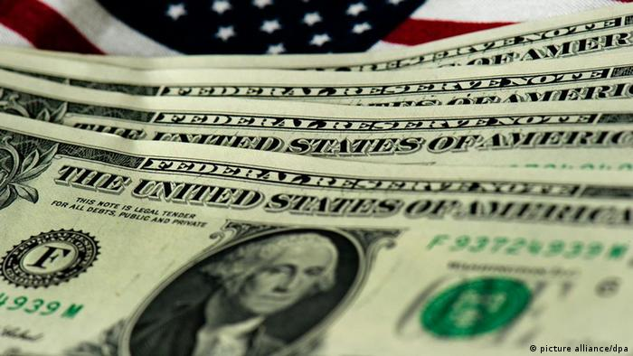 Dollars on a US flag Photo: Arno Burgi dpa/lsn