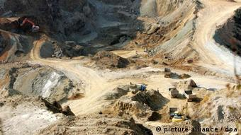 An excavator loads trucks with rare earth