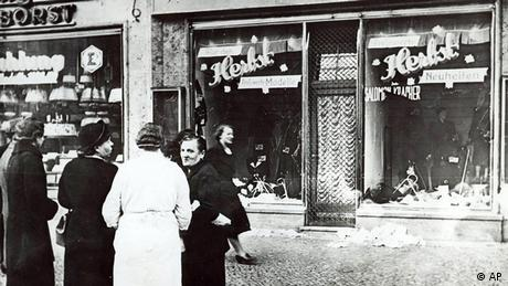 group of people stand outside a Jewish-owned shop in an unnamed German town (AP)