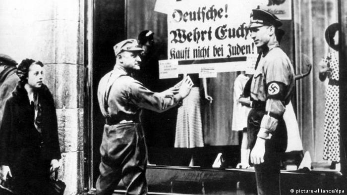 Deutschland, 1938: SA-Männer kleben während des Dritten Reiches ein volksverhetzendes Plakat mit der Aufschrift Deutsche! Wehrt Euch! Kauft nicht bei Juden an der Schaufensterscheibe eines Geschäfts, das in jüdischem Besitz ist