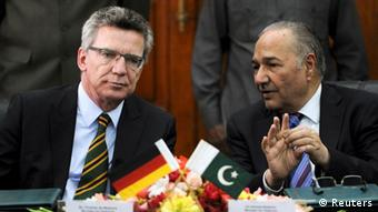 German Defense Minister Thomas de Maiziere (L) speaks with his Pakistani counterpart Ahmed Mukhtar during their meeting in Islamabad, March 13, 2012.