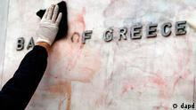 ARCHIV: ARCHIV: Ein Arbeiter reinigt nach Ausschreitungen in Athen das Logo der Bank von Griechenland von roter und schwarzer Farbe (Foto vom 14 (Foto vom 22.02.12).02.12). Die Ratingagentur Fitch hat Griechenland am Dienstag (13.03.12) auf B- heraufgestuft. Nach dem erfolgreichen Anleihentausch der vergangenen Woche sei der Ausblick nun stabil, erklaerte die Agentur zur Begruendung. Das Rating B- gilt fuer die neuen Bonds, die Athen am Montag nach dem griechischen Recht herausgab. Fuer die alten Anleihen gilt weiterhin ein C-Rating. In der vergangenen Woche hatten mehr als 80 Prozent der privaten Investoren einem Schuldenschnitt fuer Griechenland zugestimmt. (zu dapd-Text) Foto: Thanassis Stavrakis/AP/dapd