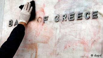 A worker cleaning the logo of the Bank of Greece (Photo: Thanassis Stavrakis/AP/dapd)