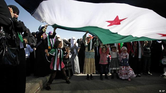 Syrian protesters chant anti-Bashar Assad slogans under a large revolutionary flag during a protest in front the Syrian embassy in Amman, Jordan, Friday, March 9, 2012. Hundreds of Syrians attend the Friday prayer, prior to a protest in front the Syrian embassy to demand International intervention and to arm the Free Syrian Army. (AP photo/Mohammad Hannon)