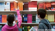 Kinder schauen sich Bücher an einem Stand der Kinderbuchhandlung am Donnerstag (15.03.2012) auf der Leipziger Buchmesse an. Zur Leipziger Buchmesse vom 15. bis 18. März werden rund 160.000 Besucher erwartet. 2071 Verlage aus 44 Ländern werben auf der Messe, die sich an Fachbesucher und Publikum wendet, für ihre Literatur. Foto: Peter Endig dpa/lsn +++(c) dpa - Bildfunk+++
