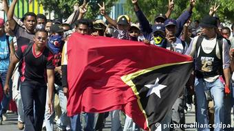 East Timorese men march through the capital city of Dili with a huge national flag 19 May 2002, ahead of East Timor's independence celebrations at midnight. (Photo: dpa)