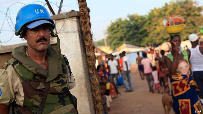 A United Nations soldier from Morocco stands guard at the entrance to the Catholic Mission, which serves as a camp for thousands of Ivorians displaced by ethnic and political clashes during the nation's six-month political stand-off, in Duekoue, in western Ivory Coast.(AP Photo/Rebecca Blackwell)