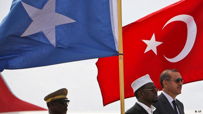 In this photo provided by the African Union-United Nations Information Support Team, Somali President Sheik Sharif Sheik Ahmed, center, and Turkish Prime Minister Recep Tayyip Erdogan, right, listen to the national anthems following Erdogan's arrival at Aden Abdulle International Airport, Mogadishu, Somalia, Friday, Aug. 19, 2011. Turkey's prime minister is in Mogadishu to visit aid camps and open a Turkish Red Crescent-run camp and field hospital. (ddp images/AP Photo/AU-UN IST, Stuart Price)
