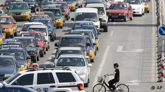 A lone woman on a bicyle in thick traffic in Beijing (Photo: ddp images/AP/Ng Han Guan)