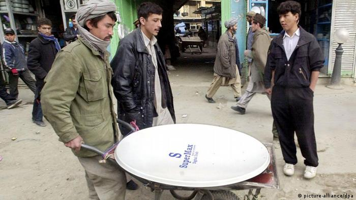 A worker moves a satellite dish, purchased by a consumer, with a wheelbarrow 21 January 2003 in Kabul after the country's supreme court banned cable television. Afghanistan's Supreme Court has imposed a nationwide ban on cable television, after cable broadcasts in several districts of the Afghan capital had offended religious leaders. Fotograf: Tauseef Mustafa dpa