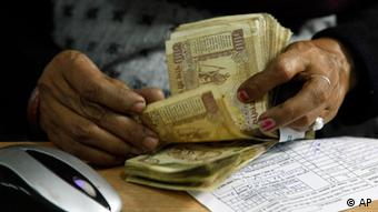 A cashier counts Indian rupee bank notes at a bank in India