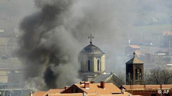 Smoke billows from Serbian Orthodox Church which was set ablaze by ethnic Albanian extremists in the northern Kosovo city of Kosovska Mitrovica, Thursday, March 18, 2004. The apparent arson followed major clashes between the rival Serb and ethnic Albanian communities in the city when ethnic Albanians tried to take control over a Serb-populated area. (AP Photo/Darko Vojinovic) ***Zu Dahmann, Der Status des Kosovo******Zu Sütfeld, Nur fürs Protokoll - UN-Sicherheitsrat debattiert über das Kosovo***
