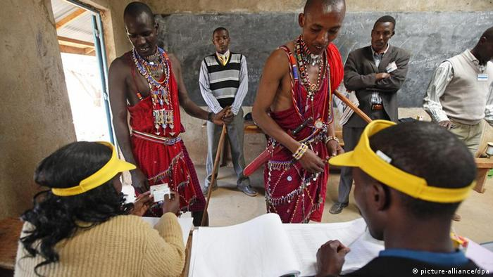 Two Maasai men have their identifications checked by electoral stuff prior to voting on the draft constitution at a polling station