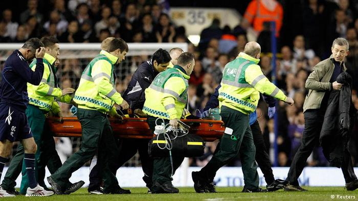 Bolton Wanderers manager Owen Coyle (L) walks alongsde the stretcher as medical staff attend to Fabrice Muamba after he collapsed on the pitch during their FA Cup quarter-final soccer match against Tottenham Hotspur at White Hart Lane in London March 17, 2012. Tottenham Hotspur's FA Cup quarter-final against Bolton Wanderers was abandoned on Saturday after Bolton midfielder Fabrice Muamba collapsed near the centre circle. REUTERS/Suzanne Plunkett (BRITAIN - Tags: SPORT SOCCER)
