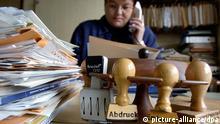 ARCHIV - Eine Frau sitzt in Straubing hinter Akten und einem Stempelhalter, während sie telefoniert (Symbolfoto zum Thema Bürokratieabbau vom 7.4.2004). Derzeit sprechen in Deutschland alle vom Abbau der Bürokratie, von der Berliner Regierung bis hin zu den Bundesländern. Ganz genau weiß es keiner, wie viele hunderte von Gesetzen und tausende von Rechtsverordnungen in Deutschland abgeschafft werden müssen, um Bürger und Wirtschaft von Bürokratie zu entlasten. Doch das Thema hat derzeit bei Politikern Konjunktur. Das Institut für Mittelstandsforschung und die Weltbank sind zu dem Ergebnis gekommen, dass den Unternehmen in Deutschland durch bürokratische Auflagen zusätzliche Kosten von jährlich 46 Milliarden Euro entstehen. Foto: Armin Weigel dpa/lsw (zu lsw-Korr: Der Kampf gegen die Bürokratie ist ein steiniger Weg vom 17.05.2006) +++(c) dpa - Bildfunk+++