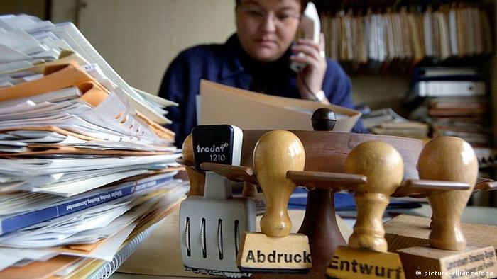 A woman sits at an overloaded desk
