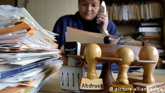 Papers and stamps symbolize bureaucracy, Copyright: picture-alliance/dpa