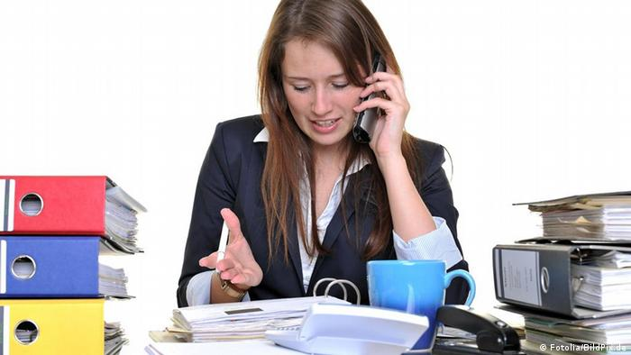 A woman at a desk surrounded by binders talks on a phone