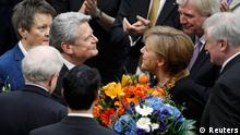 Joachim Gauck receives flowers from Chancellor Angela Merkel after he was elected German president at Germany's Federal Assembly in Berlin, March 18, 2012. German lawmakers elected Joachim Gauck, a former Lutheran pastor and human rights activist from communist East Germany, as president of the European Union's largest country on Sunday by a large majority in a first round of voting. REUTERS/Thomas Peter (GERMANY - Tags: POLITICS ELECTIONS)