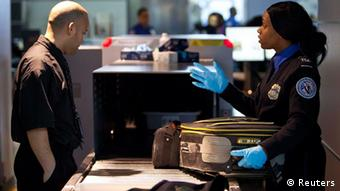 A Transportation Security Administration (TSA) security agent takes a traveler's luggage for a second security check at John F. Kennedy Airport in New York, February, 29, 2012. The TSA announced a new TSA PreCheck lane system at the airport today, allowing for an expedited screening process for travelers who volunteer more information about themselves. The system is currently in operation in nine airports throughout the United States; the TSA hopes to have the 35 busiest airports in the country utilizing the PreCheck lane system by the end of 2012. REUTERS/Andrew Burton (UNITED STATES - Tags: TRANSPORT POLITICS)