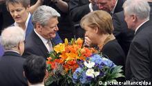 Der neue Bundespräsident Joachim Gauck (2.v.l) bekommt am Sonntag (18.03.2012) Blumen von Bundeskanzlerin Angela Merkel (CDU) nach seiner Wahl durch die Bundesversammlung im Reichstag in Berlin. 1240 Wahlleute bestimmten den neuen Bundespräsidenten. Foto: Kay Nietfeld dpa +++(c) dpa - Bildfunk+++