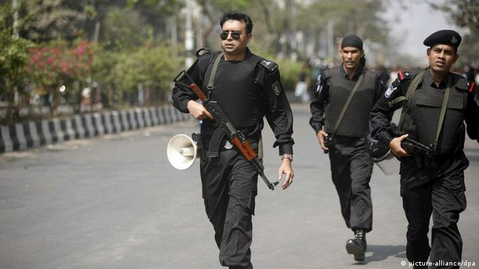 Members of the Bangladeshi Rapid Action Battalion (RAB) officials take up position in the street during a gunfire exchange