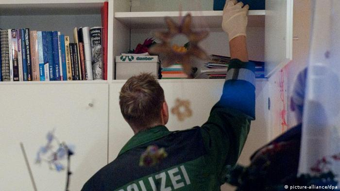 A policeman searches bookshelf in residence