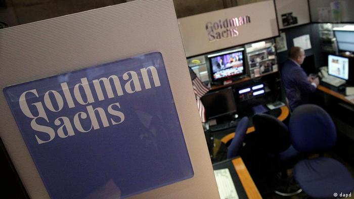 With a large Goldman Sachs logo above, a trader works in a booth on the floor of the New York Stock Exchange.