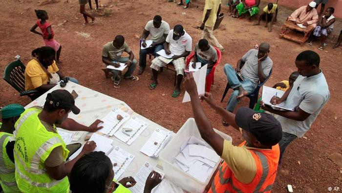 Moradores locais e observadores de partidos políticos acompanham a contagem de votos, numa assembléia ao ar livre, em Bissau. Neste domingo, os eleitores guineenses escolheram entre nove candidatos para a presidência do país.
