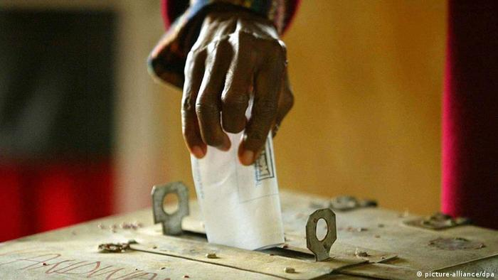 A person puts their voting slip in a ballot box