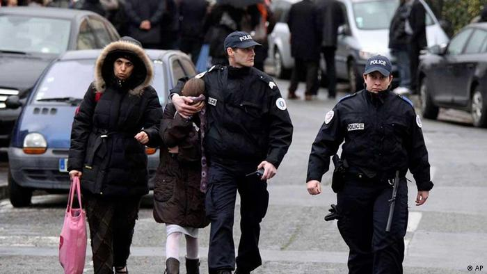 A student, second from left, is flanked by an unidentified woman and police officers as they leave a Jewish school after a gunman opened fire in Toulouse, southwestern France, Monday, March 19, 2012. A father and his two sons were among four people who died Monday when a gunman opened fire in front of a Jewish school in a city in southwest France, the Toulouse prosecutor said Monday. (Foto:Manu Blondeau/AP/dapd)