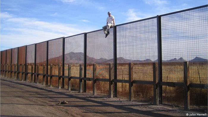 Dan Millis sitting on top of the border fence