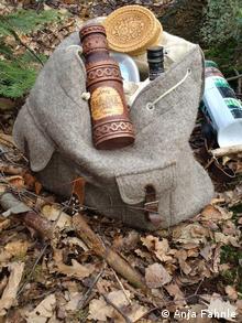 Auf einem Rucksack liegen eine Schale aus Birkenrinde, Birkenschnaps aus Minsk (Foto: DW)