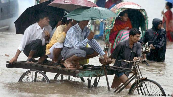 Bangladeshi commuters wade through the flooded streets of Dhaka